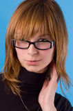 I accept these glasses?. The girl on a blue background tries on glasses Royalty Free Stock Image