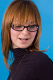 I accept these glasses?. The girl on a blue background tries on glasses Royalty Free Stock Images