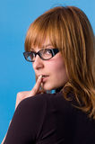 I accept these glasses?. The girl on a blue background tries on glasses Stock Photography