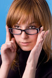 I accept these glasses?. The girl on a blue background tries on glasses Royalty Free Stock Photography