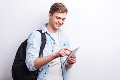 I actually love studying. Handsome young student holding digital tablet and smiling while standing against grey background Royalty Free Stock Photo