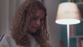 I afton h?rliga unga kopplar av kvinnan p? en soffa i hennes hemtrevliga vardagsrum arkivfilmer