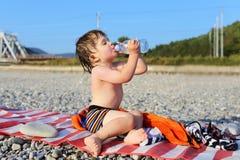 I 2 anni adorabili di acqua potabile del ragazzo sui ciottoli tirano Immagine Stock