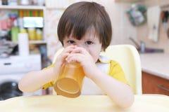 I 2 anni adorabili di bambino beve la composta della frutta secca Immagine Stock
