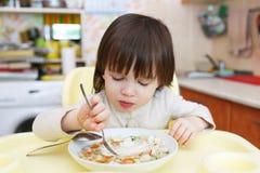 I 2 anni adorabili di bambino mangia la minestra del cavolo Fotografie Stock