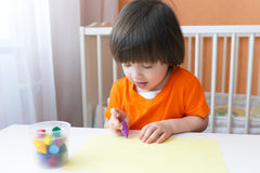I 2 anni adorabili di pittura del ragazzo con la cera disegnano a matita Immagini Stock