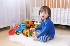 I 2 anni adorabili di ragazzo del bambino gioca le automobili Immagine Stock