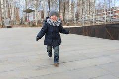 I 2 anni felici di ragazzo funziona all'aperto in primavera Fotografia Stock