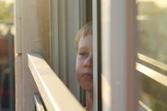 I 7 anni svegli del ragazzo guarda fuori la finestra Immagini Stock