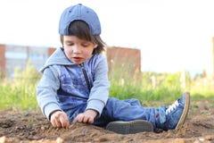 I 2 anni svegli di ragazzo gioca con la sabbia all'aperto di estate Fotografia Stock Libera da Diritti
