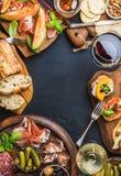 I antipasti italiani wine spuntini messi sopra il fondo nero di lerciume Fotografia Stock Libera da Diritti