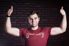 I approve. Cute young guy showing thumbs up Royalty Free Stock Photography