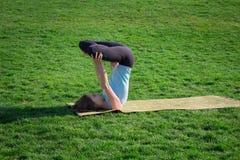 I asans di pratica di yoga di signora adatta sulla stuoia di yoga che si situa dentro gren l'erba Fotografie Stock Libere da Diritti