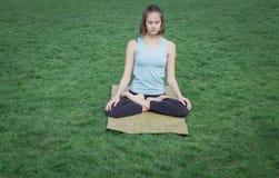 I asans di pratica di yoga di signora adatta sulla stuoia di yoga che si situa dentro gren l'erba Fotografia Stock Libera da Diritti