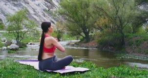 I att förbluffa naturlandskap en övande yogameditation för härlig sportig dam på det matta främst av den fantastiska sjösikten stock video