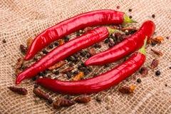 I baccelli di pepe, del peperoncini del peperoncino rosso e dei piselli roventi sul fondo della tela da imballaggio Fotografia Stock Libera da Diritti