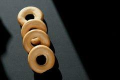 I bagel su un fondo nero, bagel limitano Immagini Stock