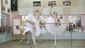 I balettkorridor är flickor i vita balettkjolar förlovade på balett, repeterar inställningen, unga ballerina som står på tår arkivfilmer