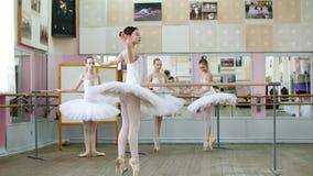 I balettkorridor är flickor i vita balettkjolar förlovade på balett, repeterar vända, unga ballerina som står på tår stock video