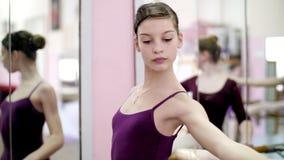 I balettkorridor utför böjer den unga ballerina i purpurfärgad body en lutning, tillbaka, lutande tillbaka och att flytta elegant lager videofilmer