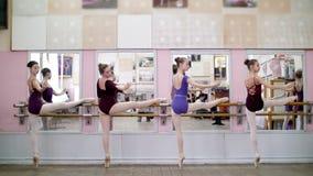 I balettkorridor utför unga ballerina i purpurfärgade body delen de behå med en lutning, böjer tillbaka, lutande tillbaka och att arkivfilmer