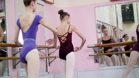 I balettkorridor utför unga ballerina i purpurfärgade body delen de behå med sträckning, sitta-UPS med ett fördjupat ben lager videofilmer