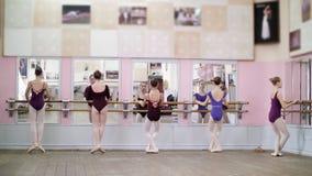 I balettkorridor utför unga ballerina i purpurfärgade body paseshappe och att gå upp som står på tår i pointeskor på stock video