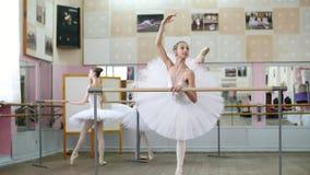 I balettkorridoren är flickan i den vita balettballerinakjolen, packe förlovad på balett, repeterar inställning, lyfter upp henne lager videofilmer