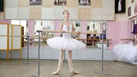I balettkorridoren är flickan i den vita packen förlovad på baletten, repeterar Roleve, går upp på tår, i pointeskor stock video