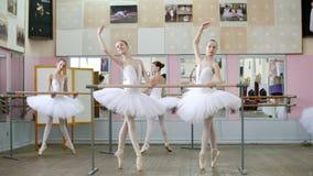 I balettkorridoren är flickor i vita balettballerinakjolar, packar förlovade på balett, repeterar croise framåtriktat, unga balle lager videofilmer