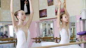 I balettkorridoren är flickor i vita balettballerinakjolar, packar förlovade på balett, repeterar delen de behå, unga ballerina stock video