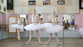 I balettkorridoren är flickor i vita balettballerinakjolar, packar förlovade på balett, repeterar plie framåtriktat, unga balleri lager videofilmer