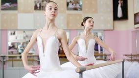 I balettkorridoren är två flickor i den vita balettballerinakjolen, packar förlovade på baletten, repeterar vända, unga ballerina arkivfilmer