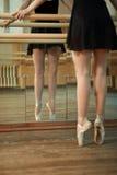 I ballerini snelli delle gambe si avvicinano alla sbarra Fotografia Stock