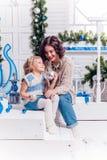 I bambini accanto ad un albero di Natale si danno i regali immagini stock