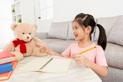 I bambini adorabili felici della ragazza che insegnano al suo orsacchiotto giocano Fotografia Stock