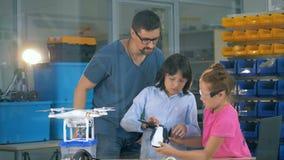 I bambini alla scuola esplorano l'elicottero, fuco con un insegnante in una classe della tecnologia stock footage