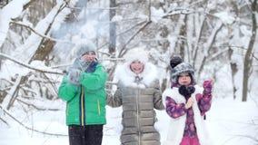 I bambini allegri della foresta dell'inverno in vestiti luminosi fanno scoppiare i cracker di natale video d archivio