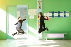 I bambini allegri saltano nel corridoio della scuola fotografia stock libera da diritti