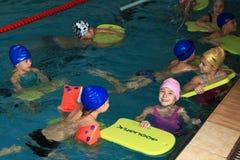 I bambini 8 anni imparano nuotare nello stagno di rivestimento. Immagine Stock