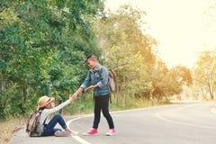 I bambini asiatici felici backpack nei precedenti della foresta e della strada Fotografie Stock Libere da Diritti
