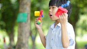 I bambini asiatici felici sta giocando il giocattolo in un parco archivi video