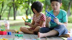 I bambini asiatici felici stanno giocando il giocattolo in un parco stock footage