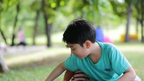 I bambini asiatici felici stanno giocando il giocattolo in un parco video d archivio