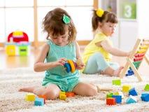 I bambini bambino e le ragazze del bambino in età prescolare giocano il giocattolo logico che imparano le forme, aritmetica e col fotografie stock
