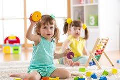 I bambini bambino e le ragazze del bambino in età prescolare giocano il giocattolo logico che imparano le forme, aritmetica e col fotografia stock