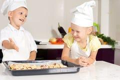 I bambini bianchi in grembiule hanno prodotto la pizza Fotografia Stock