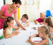 I bambini che fanno la scrittura si esercita con aiuto dell'insegnante nella classe Fotografia Stock