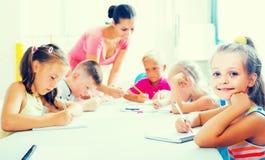 I bambini che fanno la scrittura si esercita con aiuto dell'insegnante nella classe Immagini Stock Libere da Diritti