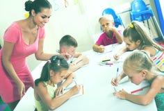 I bambini che fanno la scrittura si esercita con aiuto dell'insegnante nella classe Fotografia Stock Libera da Diritti